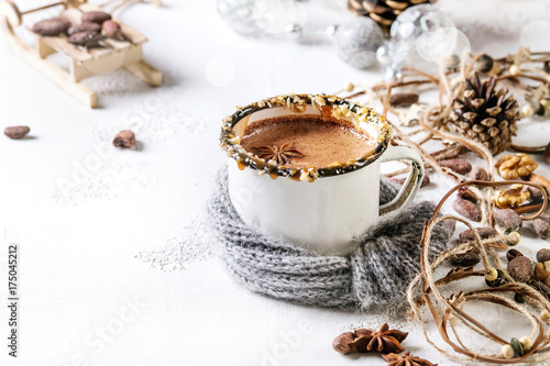 Staande foto Chocolade Vintage mug in wool scarf of hot chocolate, decor with nuts, caramel, spices. Ingredients and Christmas toys above over white texture background with space.