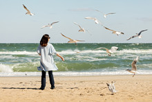 Young Woman (brunette) In A Light Blue Cardigan And Navy Jeans, With A Striped Backpack, Walks Along The Beach And Feeds Gulls.