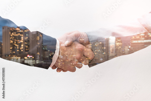 Photo The double exposure image of the business man handshaking with another one during sunrise overlay with cityscape image