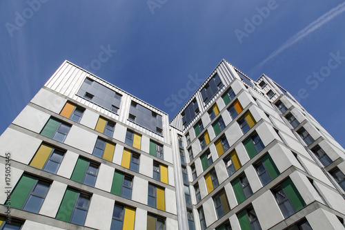 Dramatic angle of a highrise building with a blue sky background Wallpaper Mural