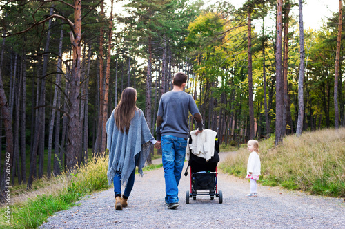 4dff4a1cbfb3 Happy young family taking a walk in a park