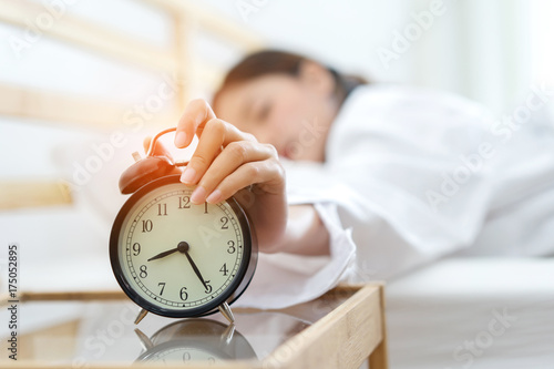 Photo Young asian woman press the button snooze wake up alarm clock alert in the morni