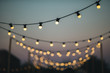 canvas print picture - Outdoors wedding decoration with light bulbs at sunset