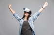 Attractive and happy woman using virtual reality goggles celebrate victory gesture on grey background. VR headset.