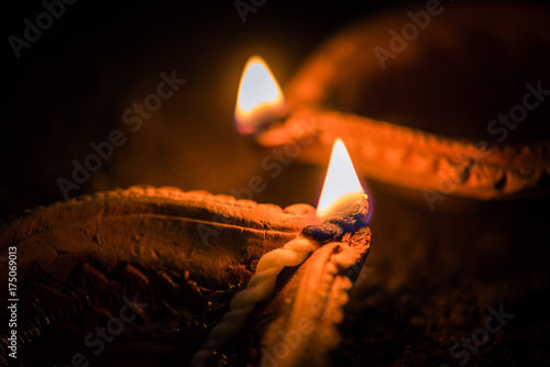 Happy Diwali - Terracotta diya or oil lamps over clay surface or ground, selective focus