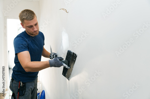home improvement - construction worker with plastering tools renovating apartment walls
