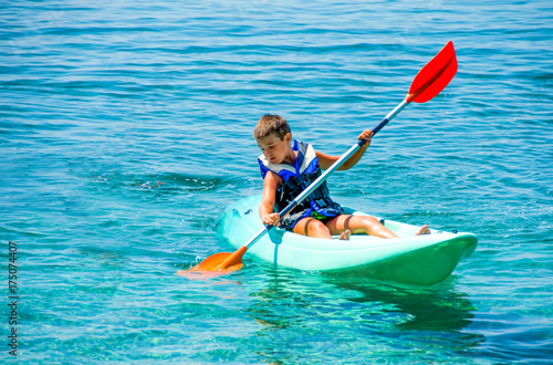 First kayaking lessons. Boy with  life buoy suit in kayak lessons during summer vacations in an island of Greece.