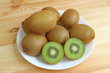 Plate of many fresh ripe kiwi fruits, both whole fruits and cross-sections, on the wooden table