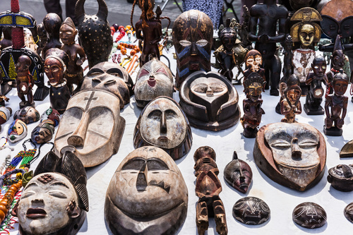 Wooden masks and figures of African culture at the flea market in Paris Wallpaper Mural