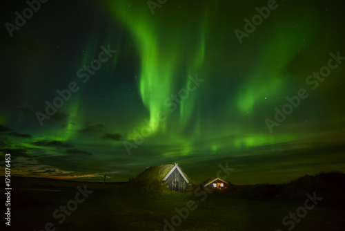 Fototapeta Nocne zdjęcie. Północne światła nad domem w starych tradycjach z trawą na dachu. Islandia.