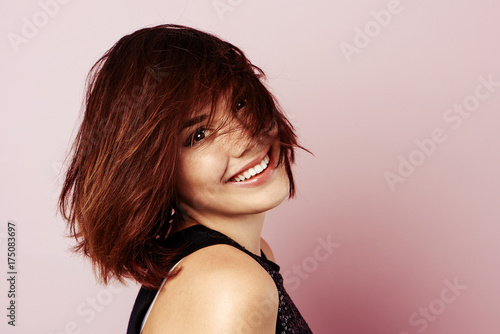 Studio portrait of pretty smiling female model with stylish hairdo over pink background.