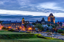Cityscape Or Skyline Of Chateau Frontenac, Park And Old Town Streets During Sunset With Illuminated Castle And Saint Denis Street Buildings