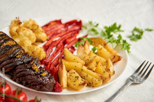 Plakat Smażone ziemniaki, bakłażan, papryka i kalafior na białym talerzu z bliska ozdobione widelcem, świeże pomidory czereśniowe i zielonej pietruszki