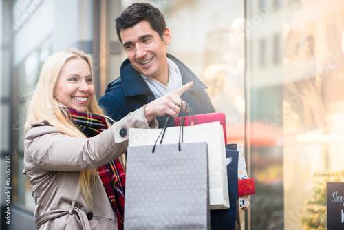 Plakat Para przed sklepowym oknem podczas zakupów na Boże Narodzenie