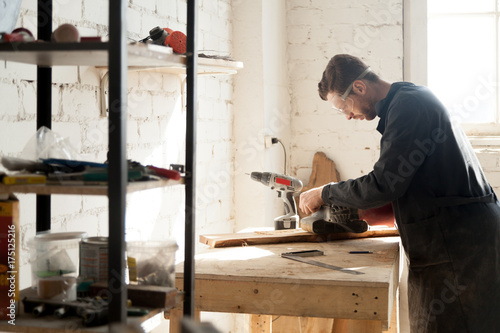 Side view of young serious joiner sanding planks, man in
