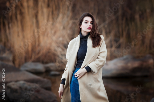 Fotografie, Tablou  Portrait of a Stylish Pretty Young Woman in Autumn Fashion Coat walking outdoors