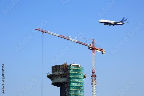 Budowa terminala na lotnisku, przelatujący samolot. Wallpaper Mural
