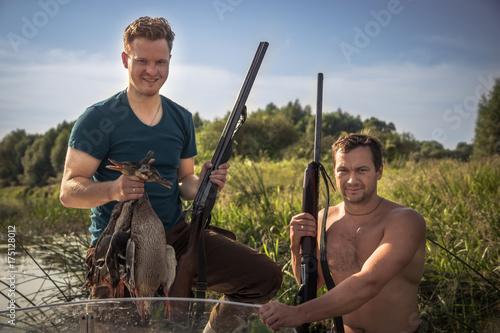 Obraz na dibondzie (fotoboard) Rozochoceni mężczyzna myśliwi z pistoletami i trofeum w łodzi na brzeg rzeki podczas łowieckiego sezonu wśród płochy