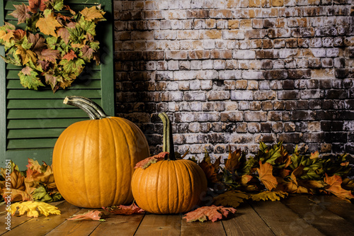 orange pumpkins and autumn leaves on wood deck with green shutter and brick wall