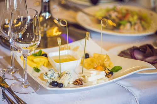 Staande foto Zuivelproducten Honey and cheeses on a white plate, food