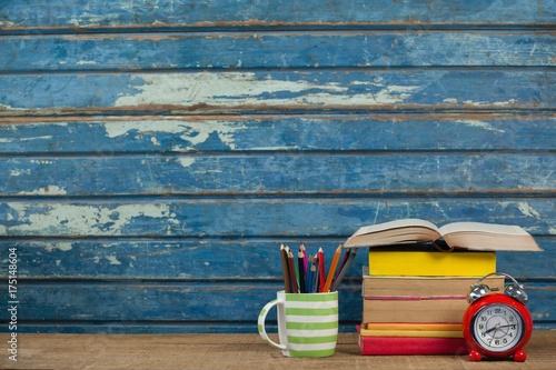 Fotografie, Obraz  Stack of books, alarm clock and pen holder