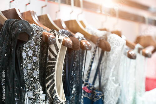 Obraz Choice of fashion clothes of different colors on wooden hangers - fototapety do salonu