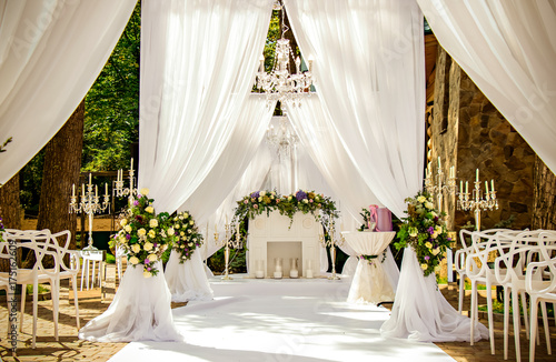 Place for wedding ceremony in white color ,with white fireplace and chandeliers decorated with flowers and white cloth and wooden chairs for guests on each side outdoors Fototapet
