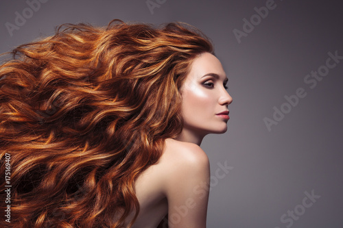 Fotografiet  Portrait of woman with long curly beautiful ginger hair.