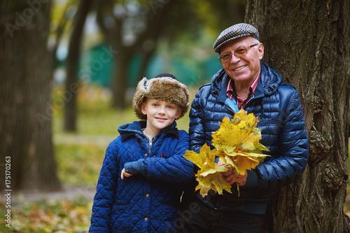 Plakat Wnuk z dziadkiem na spacerze w jesień parku. Wartości rodzinne