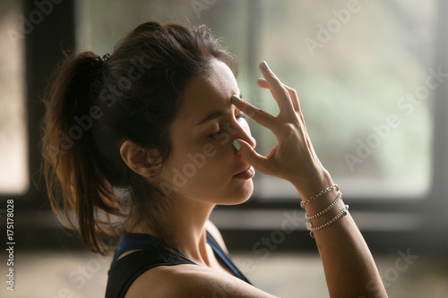 Fotografie, Obraz  Young attractive woman practicing yoga at home, making Alternate Nostril Breathi
