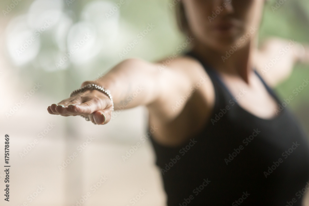 Fototapeta Young sporty woman practicing yoga at home, standing in Warrior Two exercise, Virabhadrasana II pose, working out, wearing sportswear, black top, indoor closeup, studio background, focus on hand