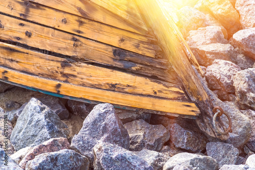 Keuken foto achterwand Schip Old wooden boat lying on stones closeup