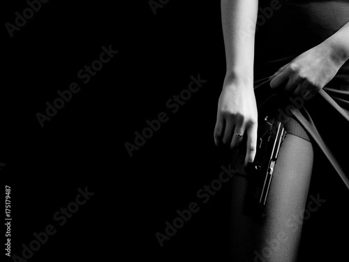 female show stockings under skirt with gun on black background with copy space Fototapeta