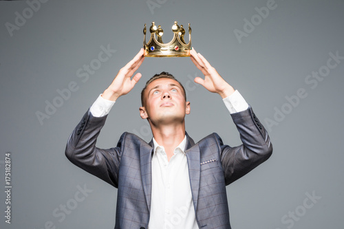 Fotografie, Obraz  Young attractive man in a suit holding above his head a golden crown on a gray b