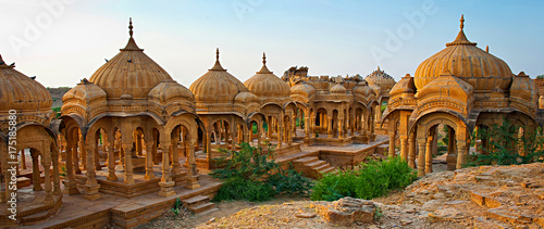 Tuinposter India The royal cenotaphs of historic rulers, also known as Jaisalmer Chhatris, at Bada Bagh in Jaisalmer made of yellow sandstone at sunset
