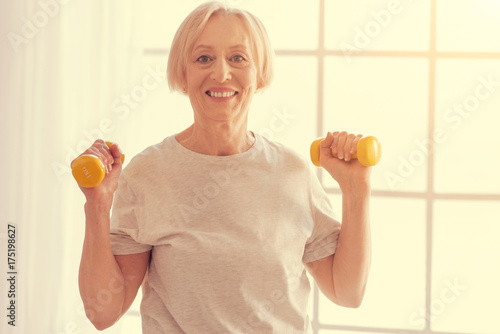 Positive senior woman exercising with dumbbells at home Canvas Print