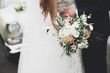 canvas print picture - Beauty wedding bouquet with different flowers in hands