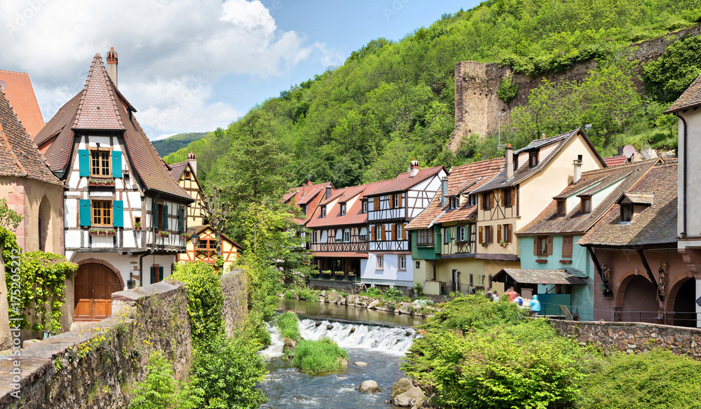 Fototapeta French traditional half-timbered houses and La Weiss river in Kayserberg village in Alsace, France