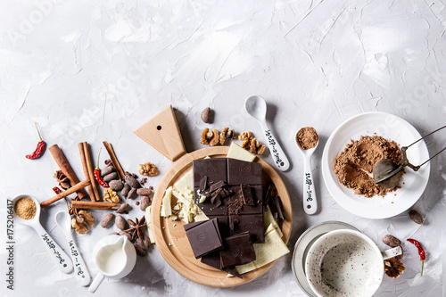Foto op Plexiglas Chocolade Ingredients for cooking hot chocolate. White and dark chopping chocolate on board, cocoa powder, cocoa beans, cream, cinnamon, sugar in spoons. Over gray texture background. Top view with copy space