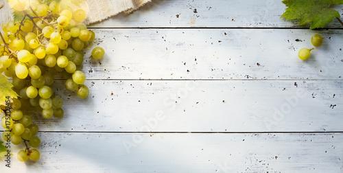 grapes on white table; seasoning vineyard background