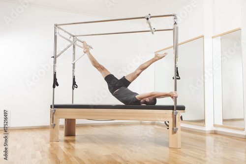 Fotografia, Obraz Pilates instructor performing exercise on cadillac equipment