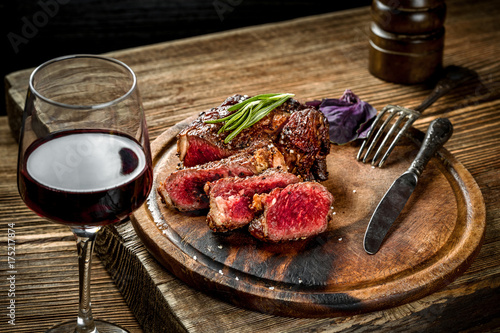 Papiers peints Steakhouse Grilled ribeye beef steak with red wine, herbs and spices on wooden table
