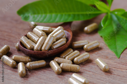 Fotografia  herbal drug in pill and capsule on wood table with green leaves .