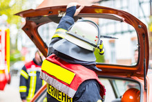 German Fireman With Helmet Holds His Hand On Car Bootlid