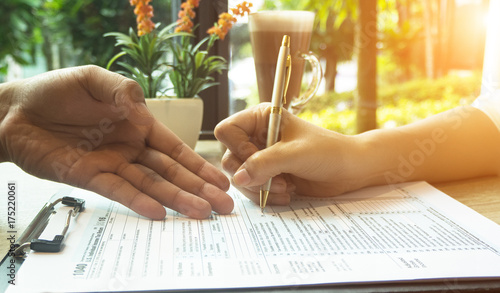 Carta da parati  The human hand with pen is signing on The Insurance Claim Form,on wooden desk,vintage tone
