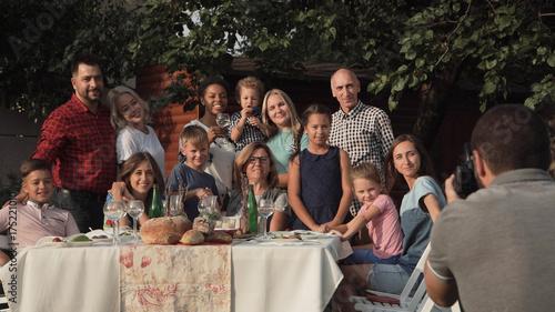 Obraz na płótnie Rozochocona rodzinna pozycja przy stołem w ogródzie i pozujący dla fotografii.