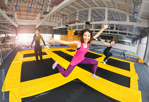 Valokuva  Cheerful and happy woman practicing and jumping on trampolines in a sports indoo