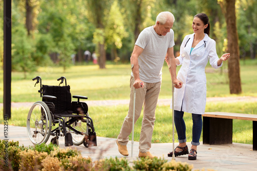Fotografía The doctor helps the patient to walk on crutches