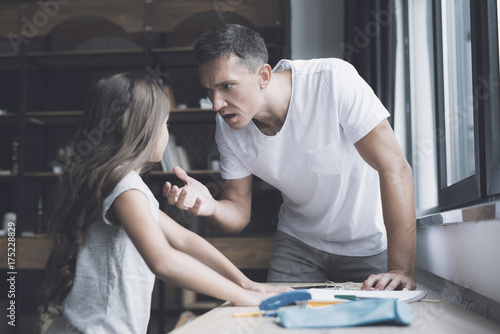 Fényképezés The father in a white T-shirt screams at his little dark-haired daughter, who st