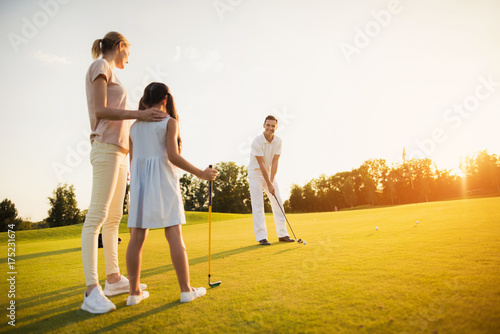 Deurstickers Golf Family playing golf at sunset. A woman and a girl are looking at a man who is preparing to make a hit